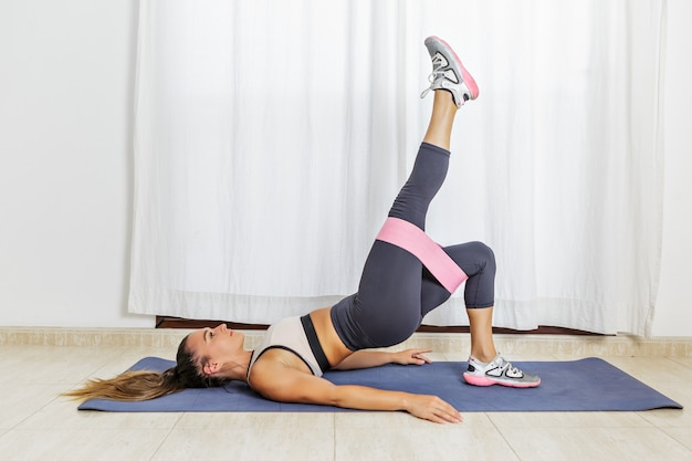 Sporty woman doing one legged bridge exercise