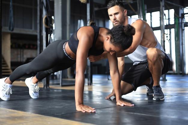 Спортивная женщина делает отжимания в тренажерном зале, ее парень наблюдает за ней.