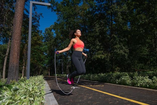 晴れた日に公園で縄跳びを使ってスキップトレーニングをしているスポーティな女性。
