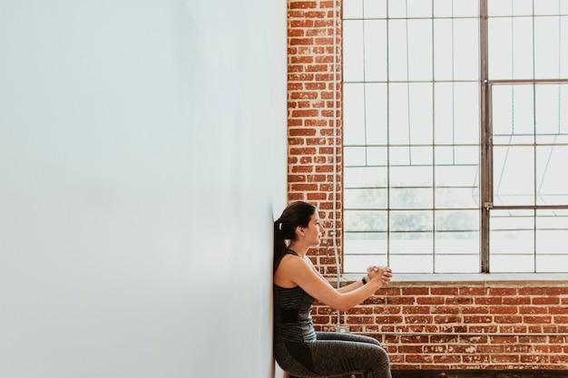 壁にスクワットをしているスポーティな女性