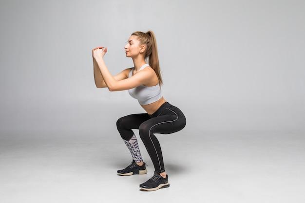 스쿼트 하 고 스포티 한 여자입니다. 흰 벽에 고립 된 군사 운동복에 근육 피트 니스 여자. 체력과 건강한 라이프 스타일 컨셉
