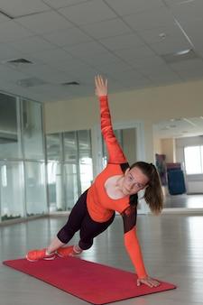 Спортивная женщина делает разминку и поднимает руку, глядя в камеру в тренажерном зале