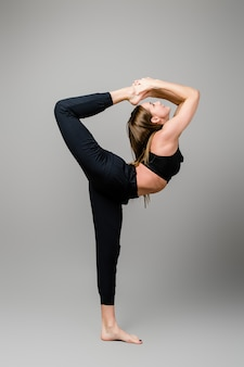 Sporty woman doing yoga isolated on grey background