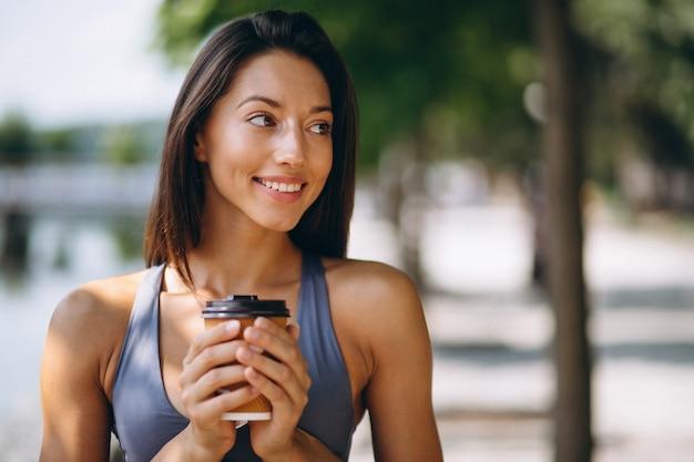 公園の中でコーヒーを飲むスポーティな女性