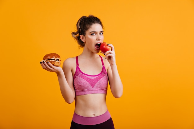 Sporty woman eats red apple on orange wall