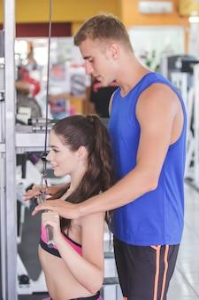 그녀의 트레이너와 함께 체육관에서 운동하는 스포티 한 여자