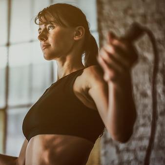 체육관에서 줄넘기로 운동하는 스포티한 여자