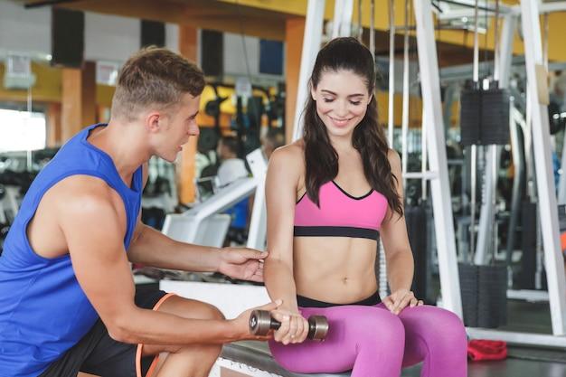 Спортивная женщина тренируется со своим инструктором в тренажерном зале