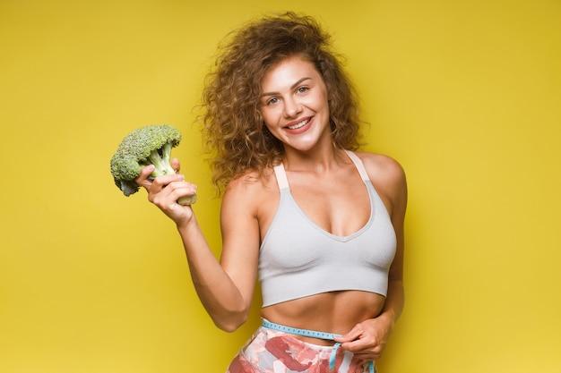 스포티한 여성 피트니스는 노란색에 큰 브로콜리를 들고 적절한 영양 섭취를 권장합니다