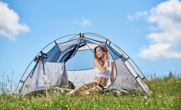 Sporty woman hiker resting in tent, on the top of hill against blue sky and clouds, smiling, looking away, enjoying summer day in the mountains