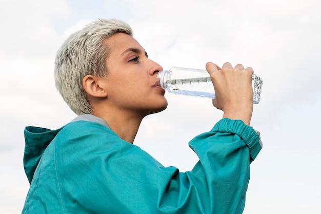 水のボトルを保持しているスポーティな女性