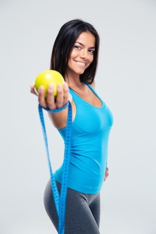 Спортивная женщина, держащая яблоко и измерительную ленту