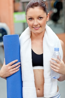 Sporty woman holding a bottle of water and an exercise mat looking at the camera