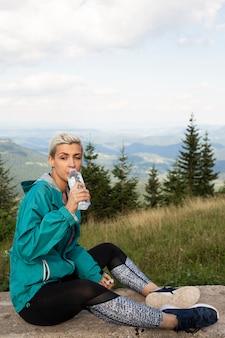 Donna sportiva che tiene una bottiglia d'acqua Foto Gratuite
