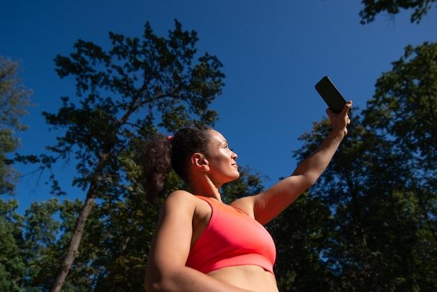 스포티 한 여자 휴대 전화를 들고 야외 joging 후 휴식을 취하는 동안 셀카 만들기. 아름다운 자연 즐기기