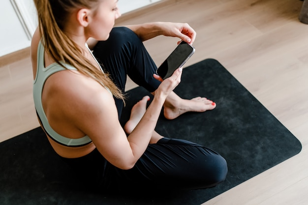 Sporty woman at home with phone on yoga mat