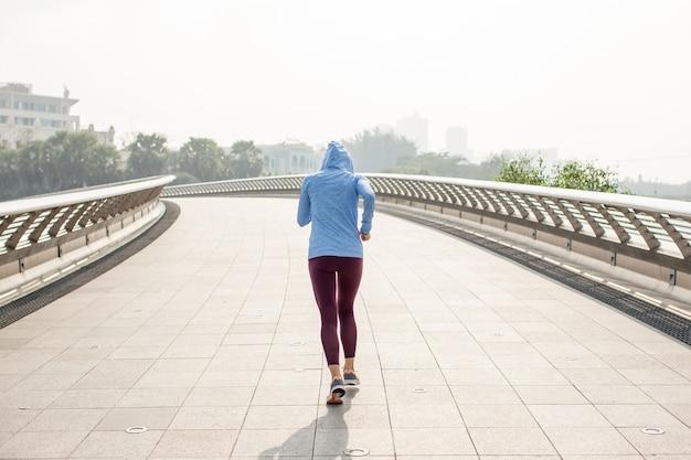 Sporty woman in hoodie running on bridge
