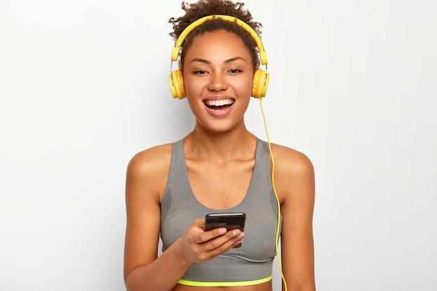 アクティブウェアのスポーティな女性は、笑顔が広く、現代の携帯電話を使用し、ヘッドフォンで音楽を聴き、白い背景でポーズをとります。