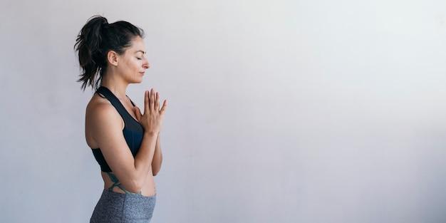 Спортивная женщина в позе анджали мудра