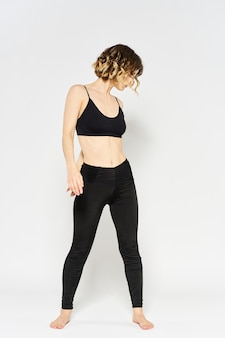 Спортивная женщина в черных джинсах и футболке делает упражнения в яркой комнате.