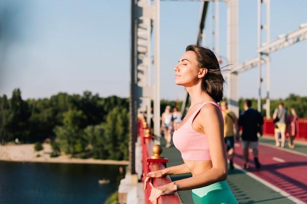 夏の天候を楽しんで周りを見回す川の景色を望むモダンな橋で日没時にスポーツウェアをフィットさせるスポーティな女性