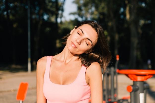 トレーニング後の前に首を伸ばしてスポーツグラウンドで日没時にスポーツウェアをフィットさせるスポーティな女性