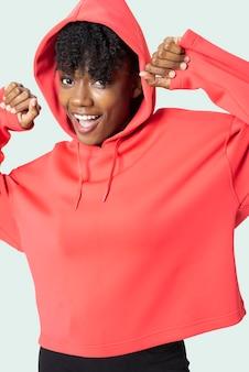 赤いパーカーの女性のアパレルの写真撮影でスポーティな女性
