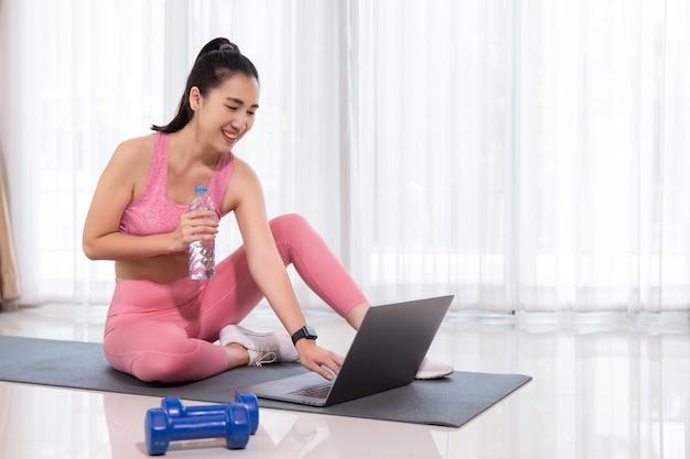 운동복을 입은 스포티 한 여성이 덤벨과 물 한 병 또는 단백질 쉐이크와 함께 바닥에 앉아 거실에서 집에서 노트북을 사용하고 있습니다.
