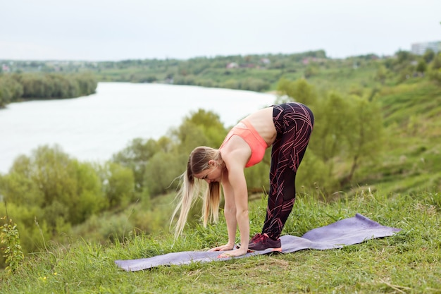 Sporty woman is doing fitness exercises on the bank of the river.