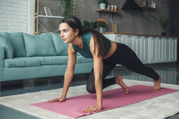 Sporty woman is doing fitness exercises planking at home on the floor