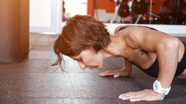 스포티한 여성이 체육관 바닥에서 클로즈업을 하고 있습니다. 그녀는 팔을 더 벌리고 팔굽혀펴기를 계속하고 있습니다. 운동 및 스포츠 개념, 햇빛