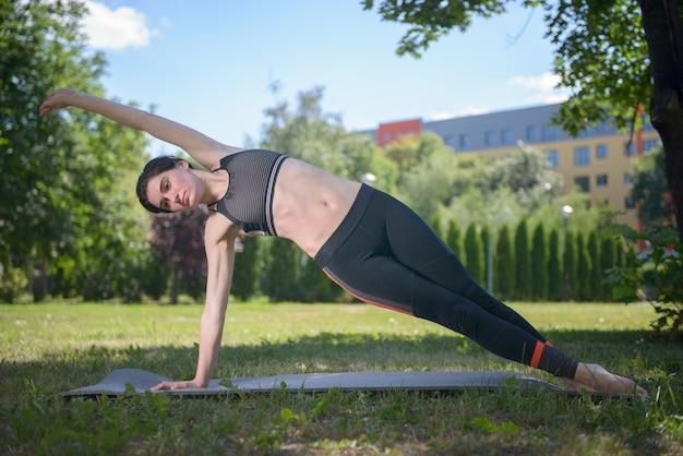 Спортивная женщина занимается йогой, занимается гимнастикой в парке.