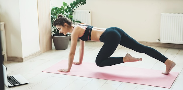 Спортивная женщина занимается настилом дома с помощью ноутбука и улыбается в спортивной одежде