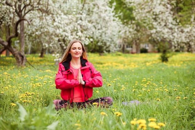 スポーティな女性は、春に咲く木々の間の緑の芝生に座って瞑想を練習しています。