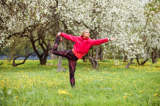 Sporty woman is practicing yoga outdoors in the park in spring.