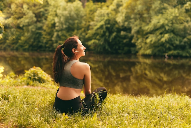 Sporty woman is taking a break for recovery near a lake in lotus pose while listening through earphones.