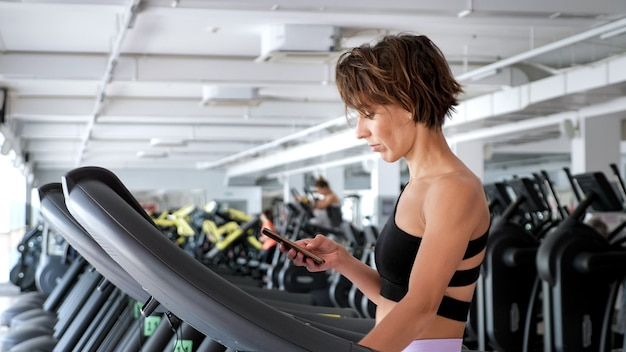 스포티한 여성이 체육관에서 러닝머신에서 훈련하고 스마트폰을 보고 있습니다.