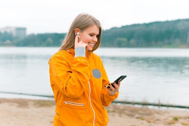 스포티 한 여성이 걷고 있고 숲의 호수 근처에서 이어폰과 휴대 전화를 사용하고 있습니다.