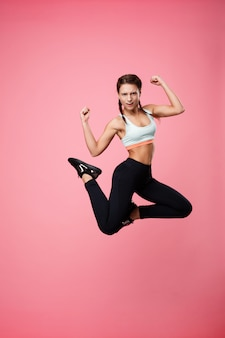 Sporty женщина прыгает, делая позы, глядя прямо на розовый