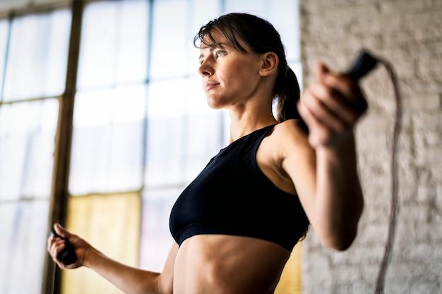 Спортивная женщина прыгает через скакалку в тренажерном зале