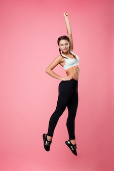 Sporty woman jumping up making fun isolated on pink