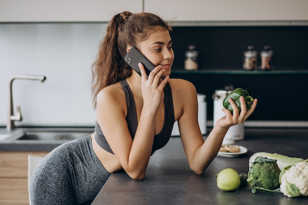 Sporty woman at kitchen using mobile phone