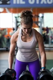 Спортивная женщина, поднимающая гантели