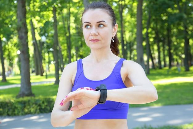 스포티 한 여자는 그의 손에 시계를 본다