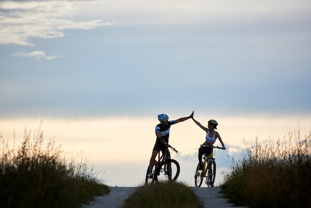 Sporty woman and man riding bicycles, having fun outside. silhouettes of sportsmen highing five and posing on road in sunset time. non urban scene.