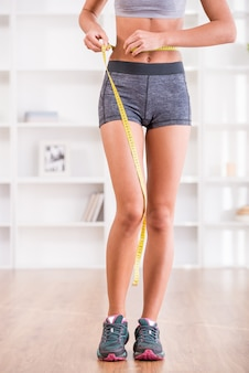 Sporty woman and measure around her body at home.