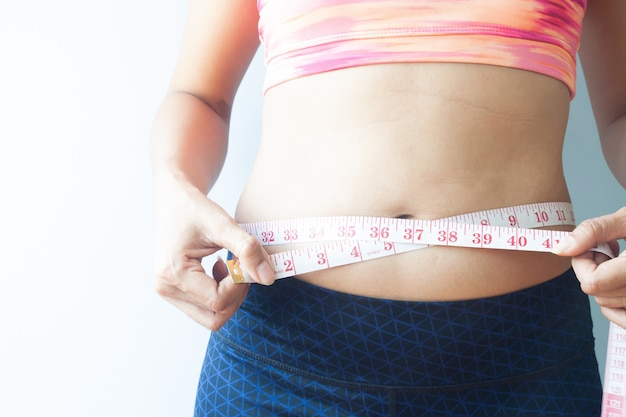 Sporty woman measuring body, get rid of belly fat. healthy concept