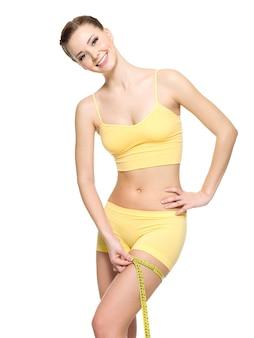 Anca di misurazione della donna sportiva con nastro adesivo dopo fitness - isolato su bianco