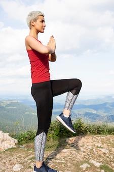 自然の中で瞑想するスポーティな女性