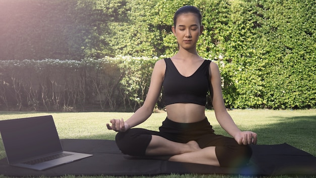 A sporty woman or online instructor in sportswear is sitting and practicing yoga on the mat